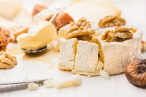 Cheese pieces with walnuts and dried fig — Stock Photo