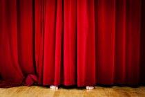 Vista de pies detrás de la cortina roja de recorte - foto de stock