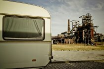 Industrial factory building and cropped part of travel car — Stock Photo