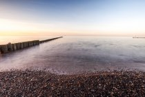 Row of wooden poles and sunset seascape — Stock Photo