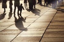 People silhouettes and shadows on tiled street at sunset — Stock Photo