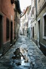 Small town houses and street road with puddle — Stock Photo