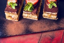 Cakes with strawberries and chocolate powder — Stock Photo
