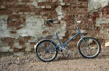 Little bicycle parked in street near old brick building wall — Stock Photo