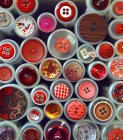 Closeup top view of different patterned buttons on plastic containers — Stockfoto