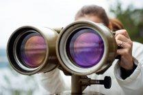 Ritagliate la vista della donna che guarda in grande binocolo — Foto stock