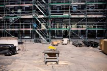 Construction site with saw, piled metal constructions and working men on scaffolds — Stock Photo
