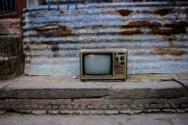 Daytime view of old TV set near shabby building wall — Stock Photo