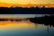 Hermosa vista panorámica del lago contra la nieve cubierto cumbres al atardecer - foto de stock