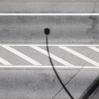 Gray asphalt road with white lines and street lamp shadow — Stock Photo