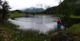 Back view of woman standing and looking at pond in mountains — Stock Photo