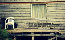 Facade of old wooden hut, chair and ladder by the window — Stock Photo