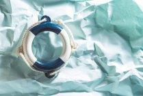 Kleinen Rettungsring auf blauem zerknittertes Papier — Stockfoto