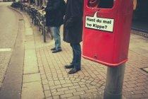 Avaloir rouge avec texte en allemand et des gens debout à proximité, Hamburg, Germany — Photo de stock