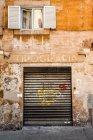 Old building facade with window and garage rolling door — Stock Photo