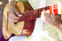 Closeup partial view of guitarist playing guitar in sunlight — Stock Photo
