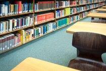 Biblioteca de la Universidad con libros y escritorios - foto de stock