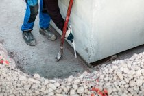 Cropped view of worker measuring interval to concrete wall — Stock Photo