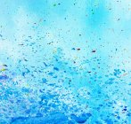 Blue surface with blots of different paints — Stock Photo
