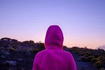 Woman in purple jacket enjoying nature beauty at sunset — Stock Photo