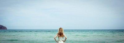 Блондинка женщина смотрит на море вид сзади — стоковое фото