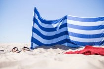 Am Meer-Szene mit Umkleideraum, Kleidung und Hausschuhe am Sandstrand — Stockfoto