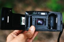 Cropped view of person hand holding analog camera — Stock Photo