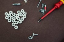 Screwdriver and screws on brown table — Stock Photo