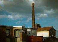 Пором труби над старими будинками невелике містечко в сонячному світлі — стокове фото