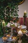 Diferentes dulces y velas en jardín - foto de stock