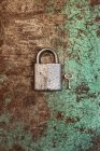 Close-up view of large lock and small key on rusty surface — Stock Photo