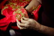 Close-up view of hands sewing traditional clothing ornament — Stock Photo