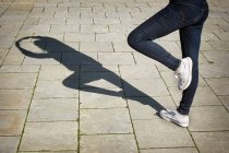 Cropped image of woman standing in yoga position on tiled pavement — Stock Photo