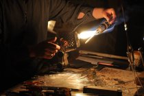 Cropped view of glassblower hands holding burner — Stock Photo
