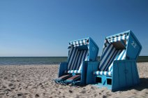 Beach chairs on sandy shore — Stock Photo