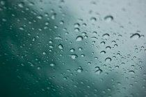Lluvia otoñal sobre la superficie de la ventana de cristal - foto de stock