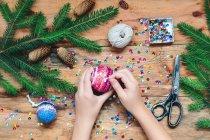 Girl making Christmas ball — Stock Photo