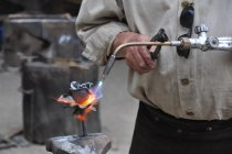 Cropped view of glassblower holding tools — Stock Photo