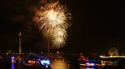 Bright golden fireworks above river water and city — Stock Photo