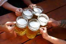 Cropped view of people holding beer mugs — Stock Photo