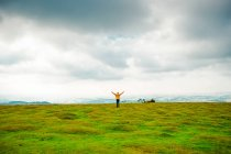 Male silhouette with hands raised in yellow jacket on a green lush meadow under cloudy sky — Stock Photo