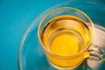 Erhöhten Blick auf Zitrus Tee mit Orangenscheibe auf Türkis Hintergrund — Stockfoto
