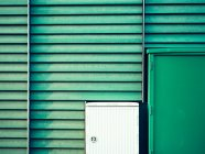 Green building facade with stripes and door — Stock Photo