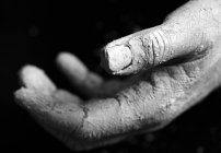 Close-up view of person hand covered with clay — Stock Photo