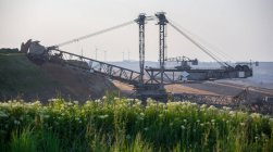 Soft coal mining scene with huge dredger and windmills on background — Stock Photo