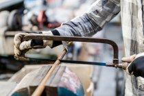 Hombre de las manos en guantes de cortar tubos de hierro - foto de stock