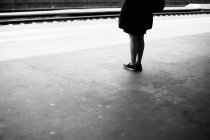 Cropped image of woman legs standing on platform and waiting, black and white — Stock Photo