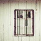 Plano exterior de fachada de edificio de madera y ventana con celosía de hierro - foto de stock