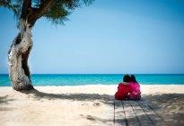 Two little kids cuddle on sandy beach under tree — Stock Photo