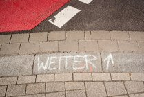 Elevated view of weiter word and arrow written with chalk on pavement stones — Stock Photo